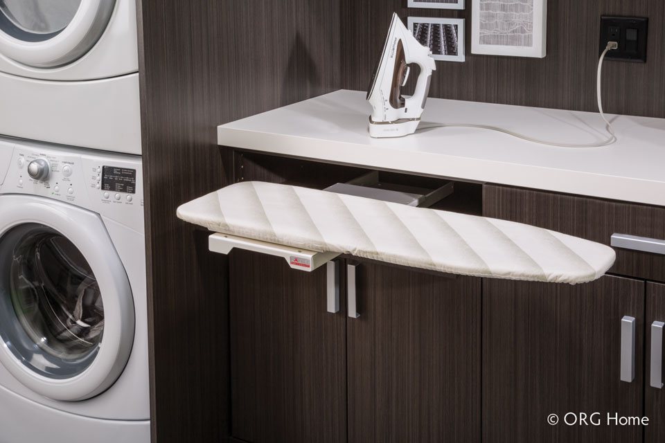 retractable ironing board in an organized laundry room